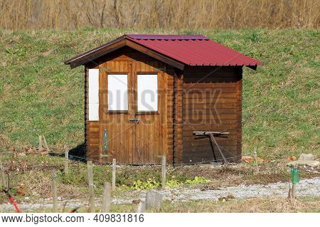 Garden Storage Tool Shed Made Of Wooden Boards And Metal Roof Tiles With Locked Doors And Two Closed