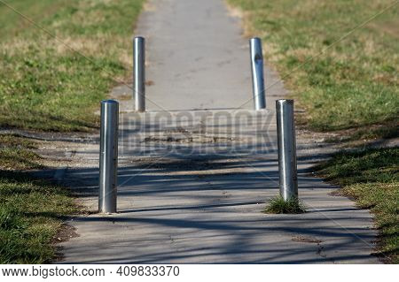 Rarely Used Old Paved Path With Cracked Asphalt And Four Broken Damaged Shiny Metal Protective Poles