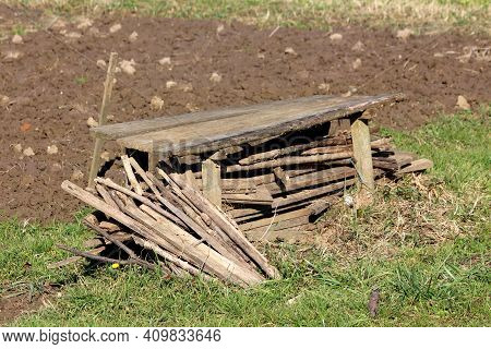 Stacked Old Broken Heavily Used Homemade Wooden Garden Stakes Mixed With Wooden Boards Next To Makes