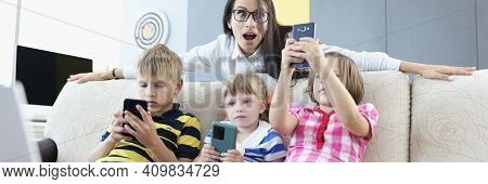 Three Children Are Sitting On Couch With Smartphones In Their Hands, Playing Online Games With Woman