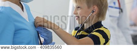 Boy In Medical Office Listens To Doctors Breath Through Stethoscope. Use Of A Stethoscope In Medicin