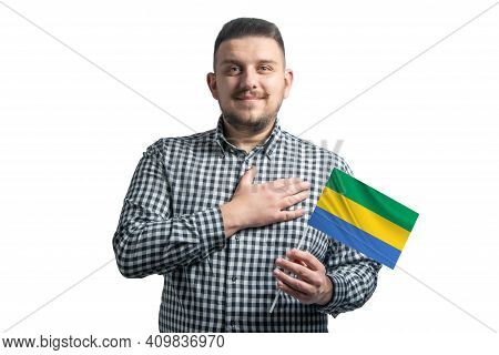 White Guy Holding A Flag Of Gabon And Holds His Hand On His Heart Isolated On A White Background Wit