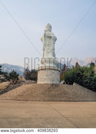 Qingdao, China - December 2017: Large White Marble Statue Of Guanyin Bodhisattva At The Entrance To