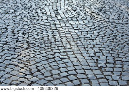 Old Cobble Stone Street. The Black Paving Stones Close Up. The Texture Of The Old Dark Stone. Vintag