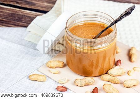 Fresh Homemade Crunchy Peanut Butter With Nuts On Light Wooden Background In The Kitchen.