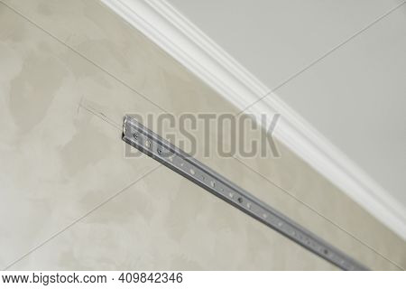 Close-up Of Stainless Steel Mounting Rail For Mounting Kitchen Cabinets On A Wall.