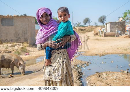 Rajasthan. India. 07-02-2018. Portrail Of A Female Adolescent Carrying Her Litthe Brother On Her Arm