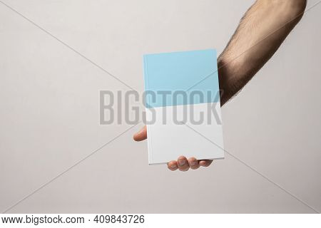 Male Hand Holding A Closed Book-catalog With Blank Cover, Editable Mock-up Series Template Ready For