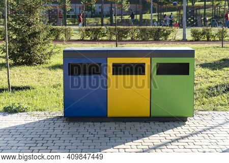 Three Colorful Recycle Bins At Urban Environment, Separately Sorting Biodegradable Trash In Differen