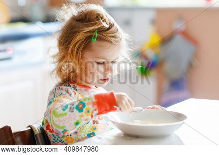 Adorable Toddler Girl Eating Healthy Porrige From Spoon For Breakfast. Cute Happy Baby Child In Colo
