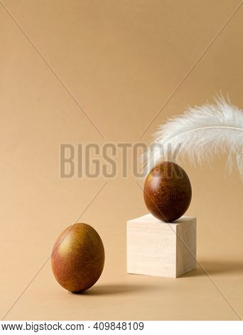 Minimalistic Easter Background. A Brown Chicken Egg Stands On A Beige Background, An Egg And A Feath