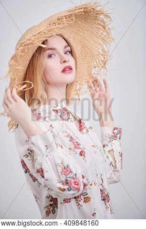 Beautiful blonde girl in a straw hat and a summer blouse on a white background. Light fresh makeup in pink colors. Spring and summer fashion.