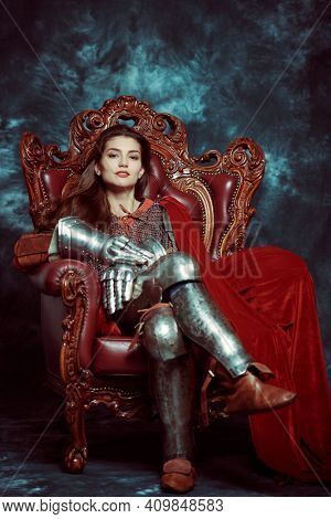Full length portrait of a medieval queen in knightly armor sitting on a throne on a grunge background. History of the Middle Ages.