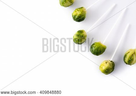 Set Of Brussel Sprouts With Lollipop Sticks On White Background.top View. Copy Space
