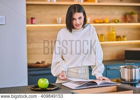 Beautiful young woman leafs through a cookbook while standing in her kitchen at home. Healthy eating and diet. Modern interior, furniture for the kitchen.