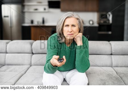 Bored Senior Woman Spends Leisure Time Watching Tv Shows, Movies. The Mature Elderly Female Sitting