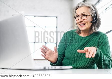 Active Mature Woman Using A Laptop For Remote Work From The Home Office. Smiling Elderly Lady Wearin