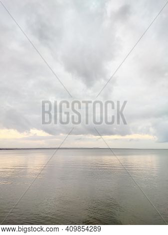 The Water Surface Of The Reservoir On A Rainy Cloudy Day. Landscape In Dark Gray Tones. Cumulus Clou