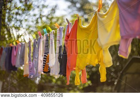 Baby Cute Clothes Hanging On The Clothesline Outdoor. Child Laundry Hanging On Line In Garden On Gre