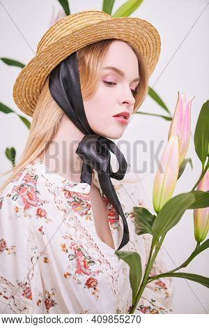 Inspiration of spring and summer. Beautiful blonde girl in a summer blouse poses with lily flowers on a white background. Light fresh makeup in pink colors. Perfume and cosmetics.