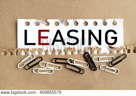 Leasing. Text On White Paper Over Torn Paper Background