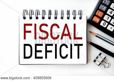 Fiscal Deficit. Text On White Notepad Paper On White Background Next To The Calculator.