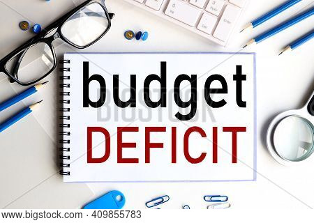 Budget Deficit. Text On White Notepad Paper On A Light Background Near The Keyboard And Glasses.
