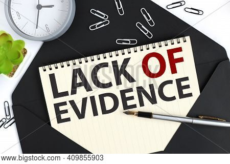 Lack Of Evidence, Text On A Sheet Of Notepad On A Black Envelope On A Light Background