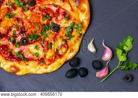 Pizza with ham and chicken on black slate board. Flat layout, top view.