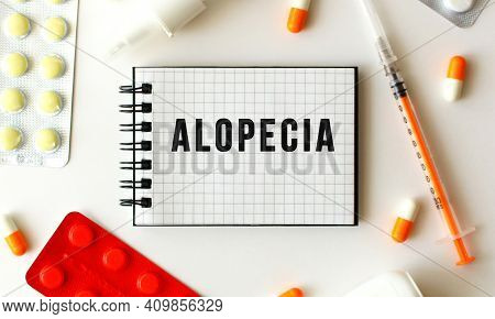 Notepad With Text Alopecia On A White Background. Nearby Are Various Medicines. Medical Concept.