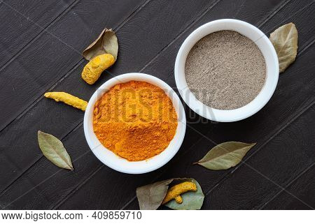 Turmeric Powder And Black Pepper Powder In White Bowls, Turmeric Roots And Bay Leaves Next To The Bo