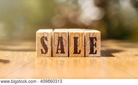 Word Sale Made With Building Wooden Blocks On Table In Sunlight.