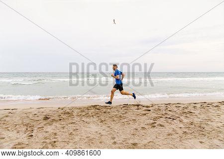 Male Jogger Run Edge Of Sea Sand Beach