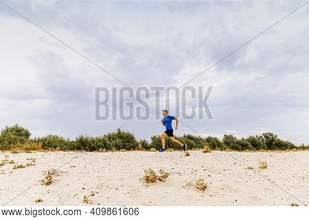 Male Jogger Running Sandy Beach In Background Evening Sky