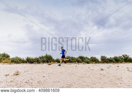 Middle-aged Male Runner Running Training On Sandy Coast