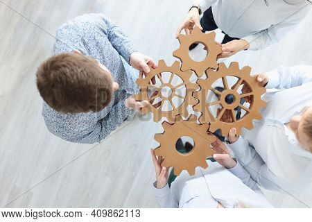 Business People Holding Wooden Gears In Office Top View. Working With Partners Concept