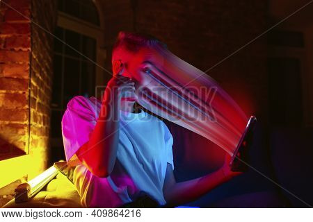 Cinematic Portrait Of Stylish Woman In Neon Lighted Interior Using A Smartphone. The Face Is Smeared