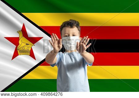 Little White Boy In A Protective Mask On The Background Of The Flag Of Zimbabwe Makes A Stop Sign Wi