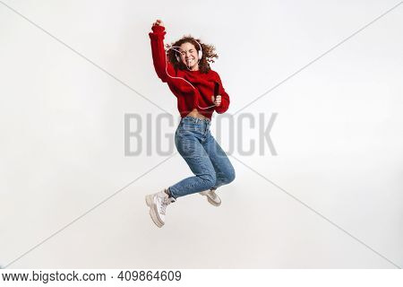 Joyful girl jumping while listening music with cellphone and headphones isolated over white background