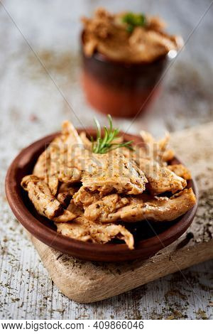 an earthenware plate with some cooked strips of spiced mock chicken meat, on a rustic wooden table next to an earthenware bowl with some more mock chicken meat strips