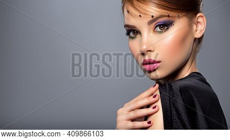 Portrait of a beautiful woman with bright makeup. Closeup model face with multicolored eye make-up. Pretty, sexy girl with creative hairstyle. Stylish fashion model with a short hair. Beauty style.