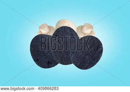 Black Potato Chips And Champignons In The Air On A Blue Background. Champignon-flavored Potato Chips
