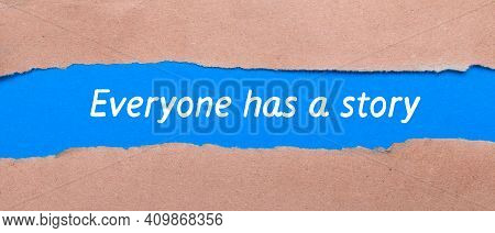 A Strip Of Blue Paper With The Words Everyone Has A Story Between The Brown Paper. View From Above