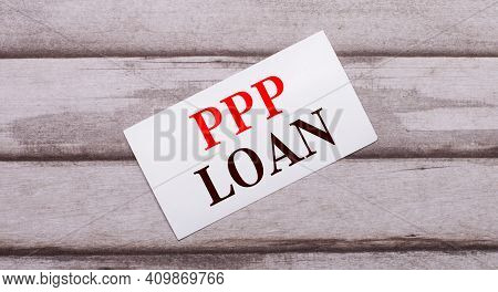 On A Wooden Background, There Is A White Card With Red Text Ppp Loan