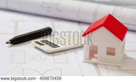 Calculator And House Model On Blueprint Background. Construction Cost Concept.