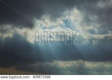 Ray Of Sunlight Escaping Among The Clouds . Sky With Sun Rays Among The Clouds . The Rays Of The Sun