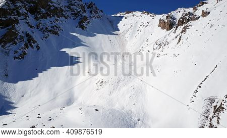 There Was An Avalanche In The Mountains. Top View From The Drone. Steep Slopes And Large Rocks. A Da