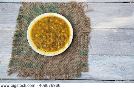 Ghugni Curry Or Curried Yellow Peas In A Plate On Burlap Fabric Isolated On White Wooden Background