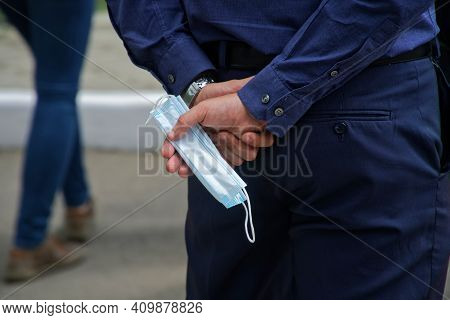 A Man, Standing In The Street, Hides A Used Medical Protective Mask Behind His Back. Pandemic Proble