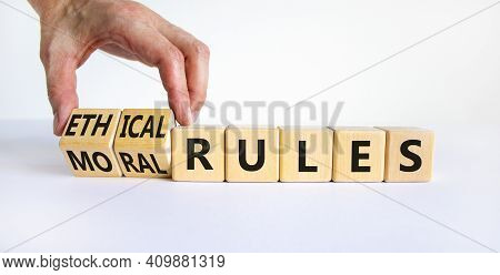 Ethical Or Moral Rules Symbol. Businessman Turns Wooden Cubes And Changes Words Ethical Rules To Mor